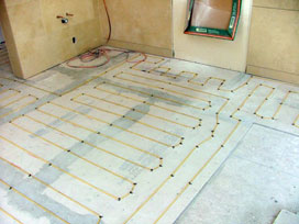 WarmQuest's heated floor products heating tile in a bathroom